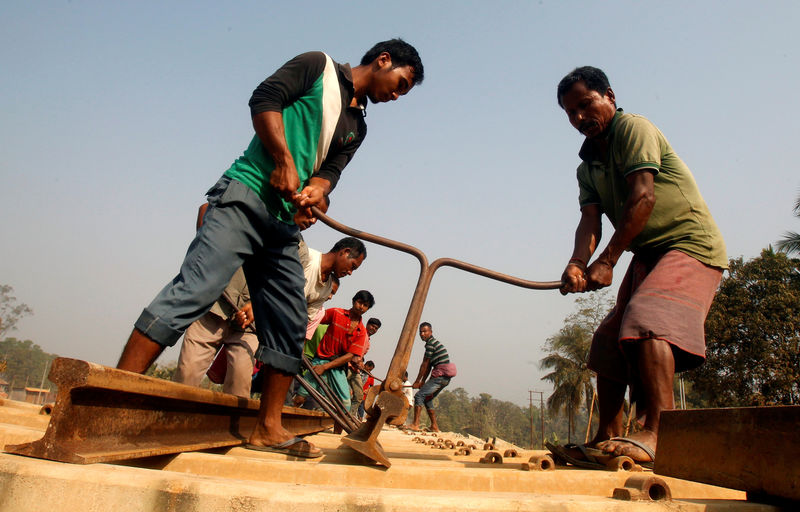 © Reuters. FILE PHOTO: Labourers work at the installation site of a new railway track on the outskirts of Agartala
