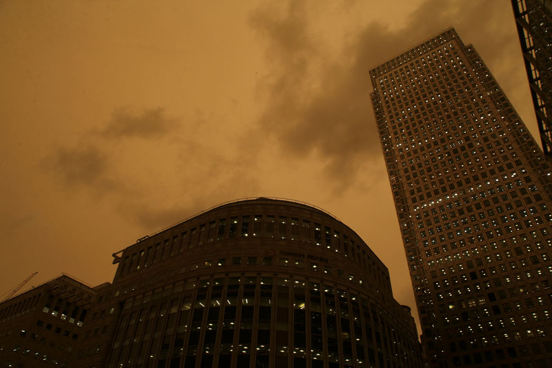 © Reuters. The sky turns red over buildings in Canary Wharf as dust from the Sahara carried by storm Ophelia filters sunlight over London