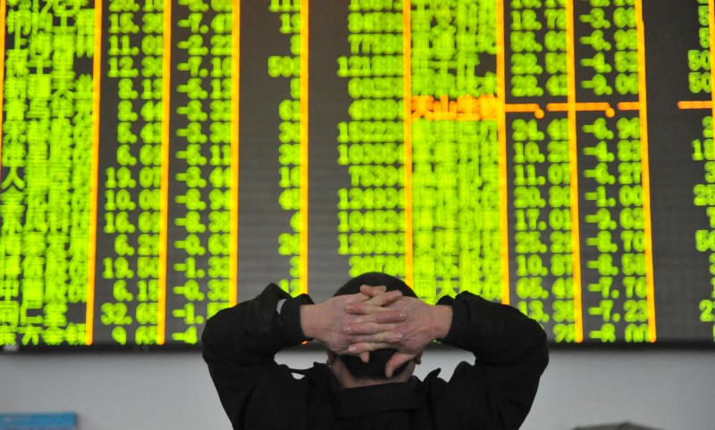© Reuters. FILE PHOTO: An investor looks at an electronic screen at a brokerage house in Hangzhou