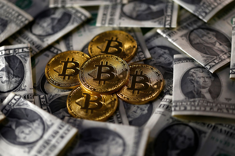 © Reuters. Bitcoin (virtual currency) coins placed on Dollar banknotes are seen in this illustration picture