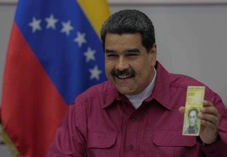 © Reuters. Venezuela's President Maduro holds a 100,000 bolivar note as he speaks during a meeting with ministers in Caracas
