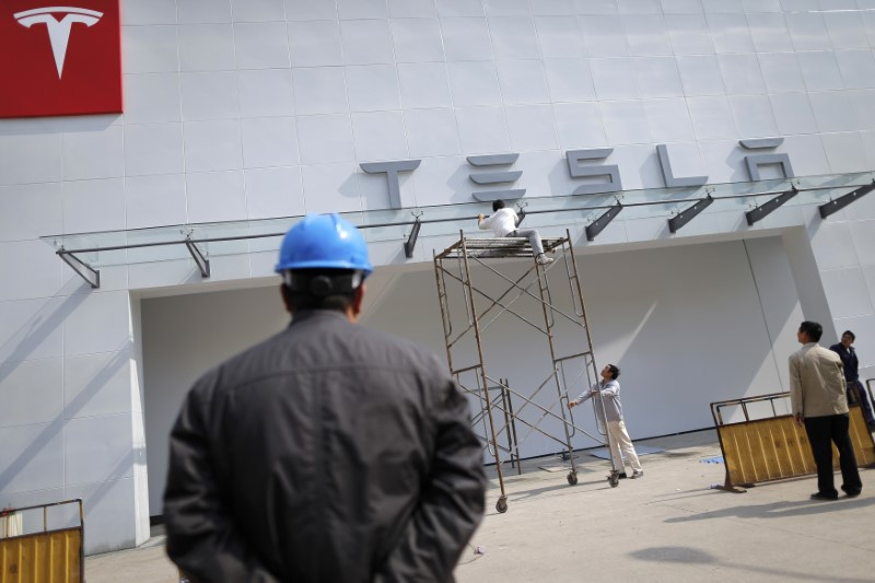 © Reuters. Labourers work on exterior of new Tesla showroom in Shanghai