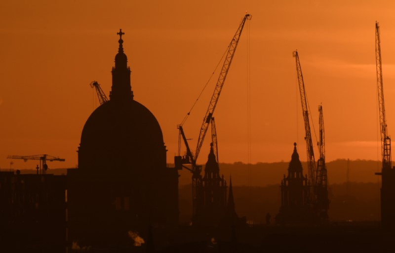 © Reuters. Construction cranes are seen by St Paul's cathedral at dawn in London