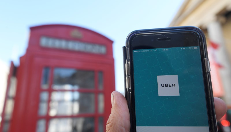 © Reuters. A photo illustration shows the Uber app logo displayed on a mobile telephone, as it is held up for a posed photograph in central London