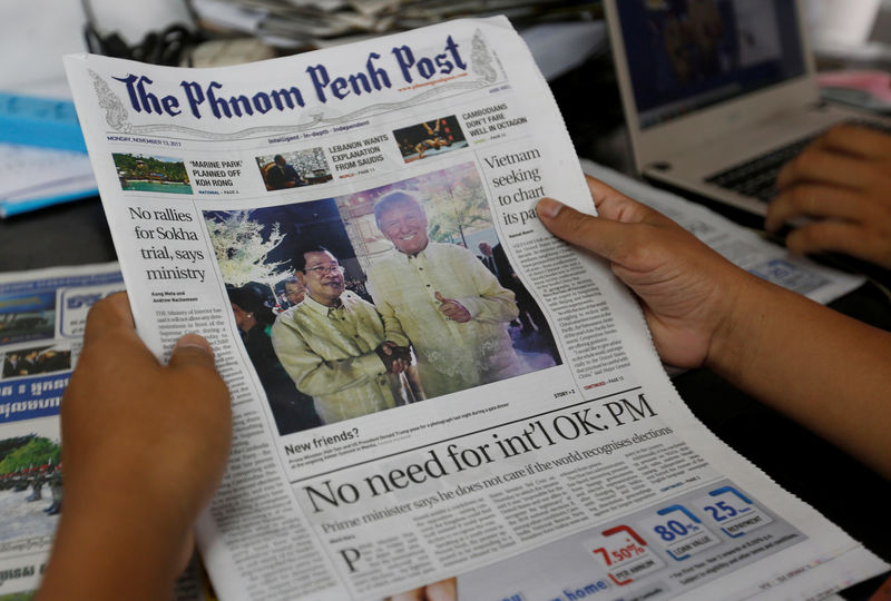 © Reuters. A newspaper shows a picture of Cambodia's Prime Minister Hun Sen, who shakes hands with U.S. President Trump during a gala dinner at the ongoing ASEAN Summit in Manila, in Phnom Penh