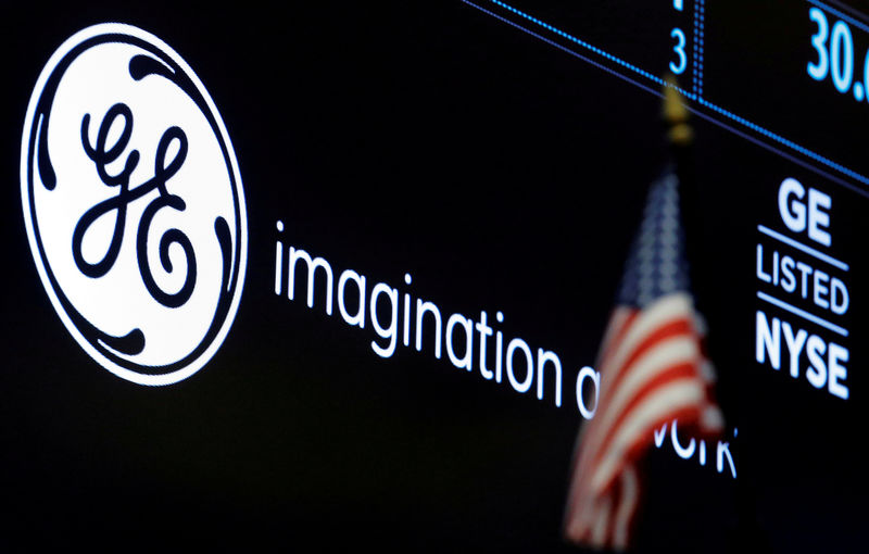 © Reuters. FILE PHOTO: The ticker and logo for General Electric Co. is displayed on a screen at the post where it's traded on the floor of the NYSE