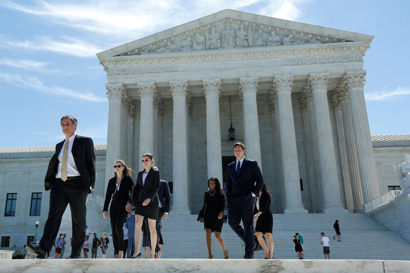 © Reuters. FILE PHOTO: People walk out after the U.S. Supreme Court granted parts of the Trump administration's emergency request to put his travel ban into effect immediately while the legal battle continues, in Washington