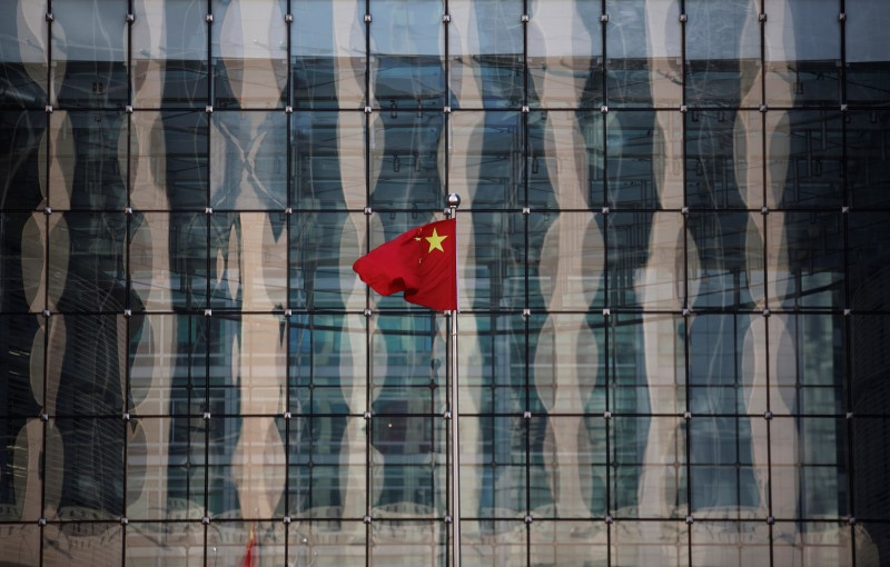 © Reuters. Chinese national flag flutters at the headquarters of a commercial bank on a financial street near the headquarters of the People's Bank of China, China's central bank, in central Beijing
