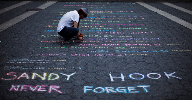 © Reuters. FILE PHOTO:    Street artist Panzarino prepares a memorial as he writes the names of the Sandy Hook Elementary School victims during the six-month anniversary of the massacre, at Union Square in New York