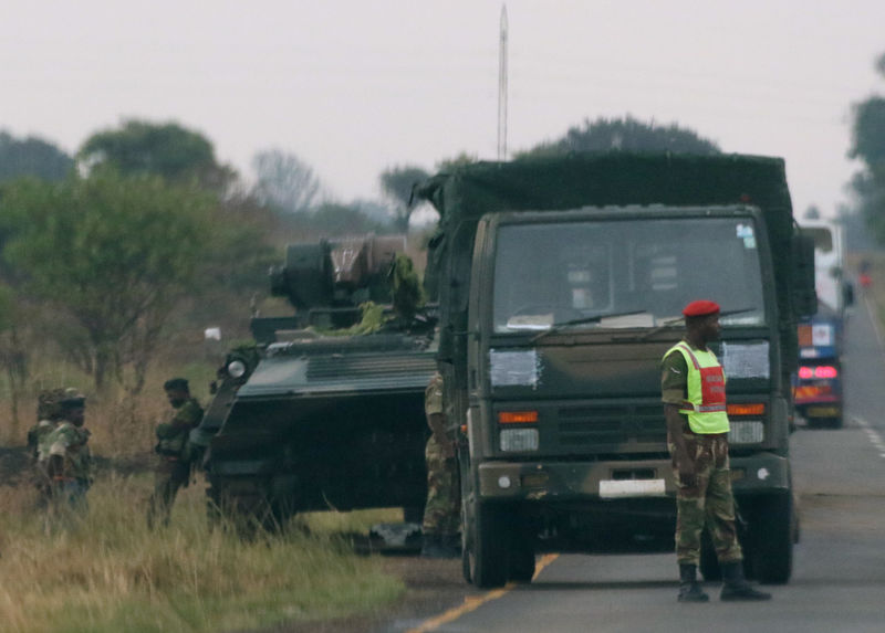 © Reuters. Soldiers stand beside military vehicles just outside Harare,Zimbabwe