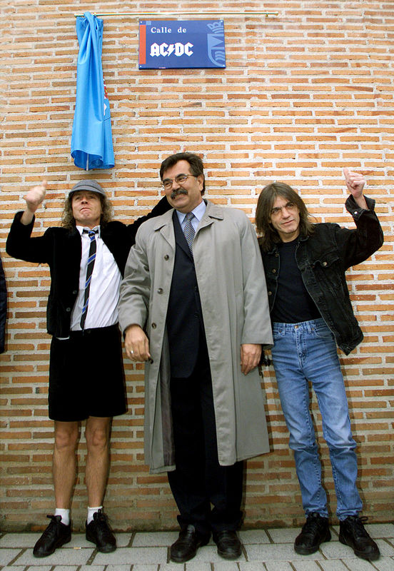 © Reuters. Angus and Malcolm Young, founder members of AC/DC, flank Jose Luis Perez, mayor of the Madrid district of Leganes, following the inauguration of a new street with the group's name, in Leganes