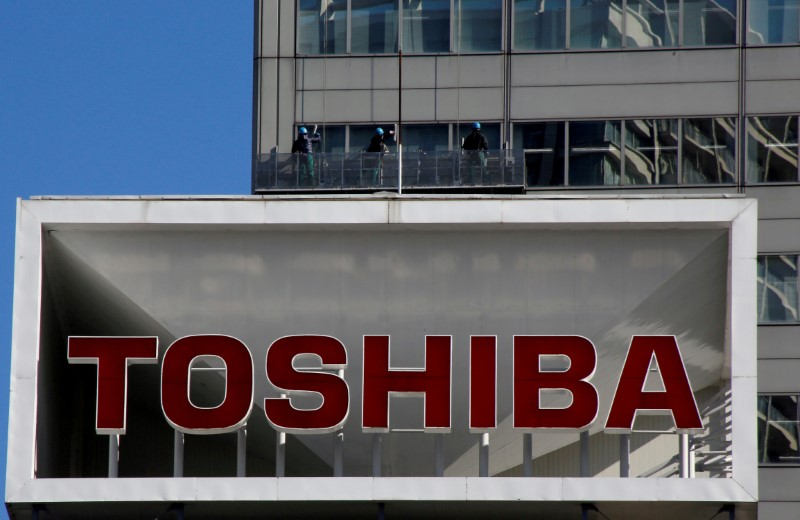 © Reuters. FILE PHOTO: Logo of Toshiba Corp is seen as Window cleaners work on the company's headquarters in Tokyo