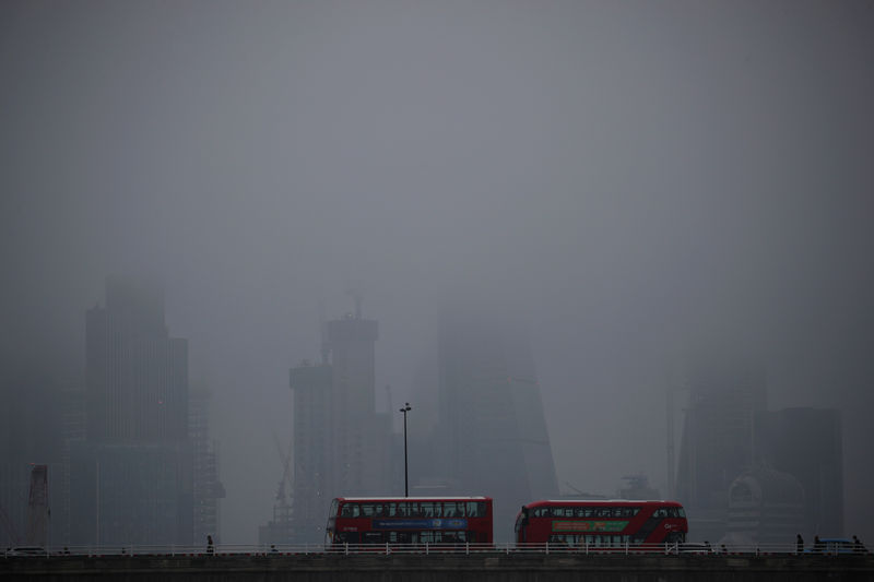 © Reuters. The City of London is partly obscured by morning fog, in London