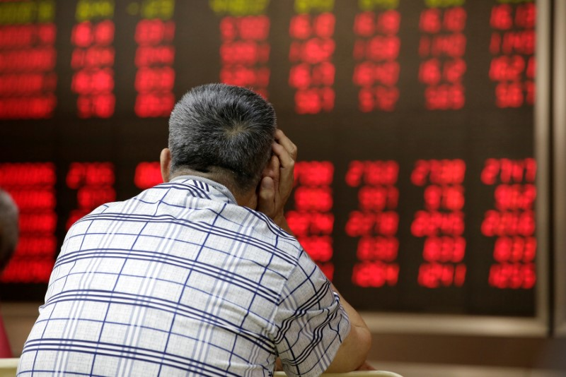 © Reuters. An investor looks at an electronic board showing stock information in Beijing