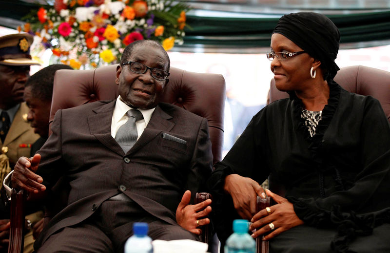 © Reuters. FILE PHOTO -  File photo of Zimbabwe President Robert Mugabe speaking to his wife Grace during the funeral of his sister, Bridget in the village of Zvimba