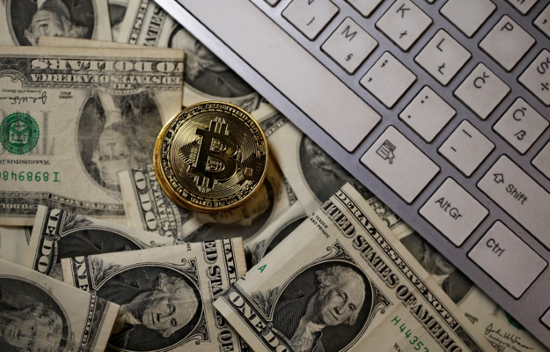 © Reuters. A bitcoin (virtual currency) coin placed on Dollar banknotes is seen in this illustration picture