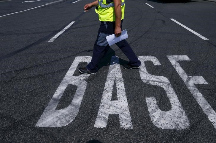© Reuters. A truck driver walks along a BASF sign on the road near the warehouse of German chemical company BASF in Ludwigshafen