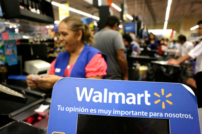 © Reuters. FILE PHOTO: Cashier smiles beyond a Walmart logo during the kick-off of the 'El Buen Fin' (The Good Weekend) holiday shopping season, at a Walmart store in Monterrey