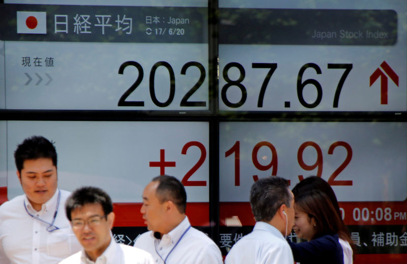© Reuters. FILE PHOTO: People walk past an electronic board showing Japan's Nikkei average outside a brokerage in Tokyo