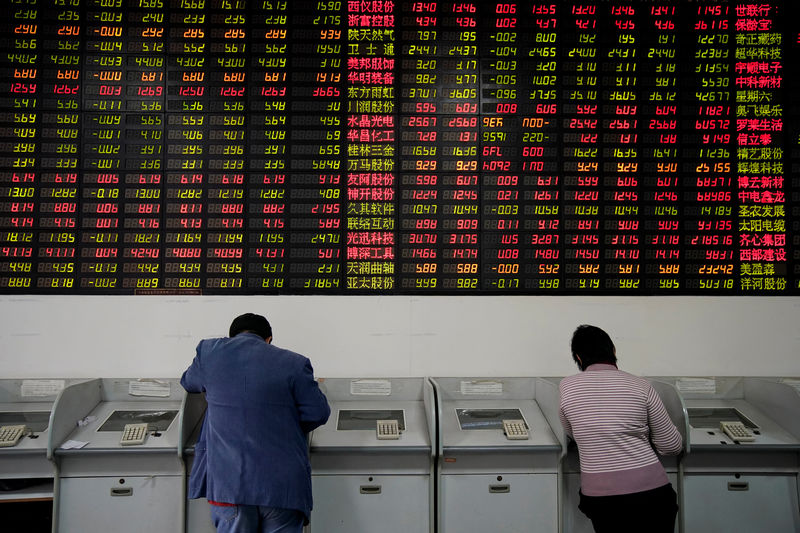 © Reuters. Investors look at computer screens showing stock information at a brokerage house in Shanghai