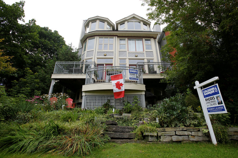 © Reuters. FILE PHOTO: A Canadian flag hangs from the deck of a house for sale in Ottawa