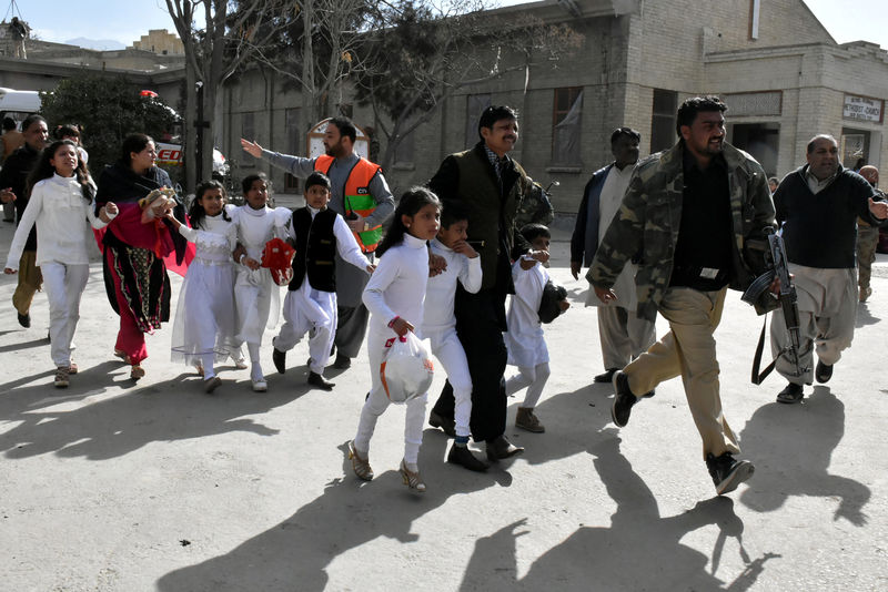 © Reuters. Policemen guide people after gunmen attacked the Bethel Memorial Methodist Church in Quetta