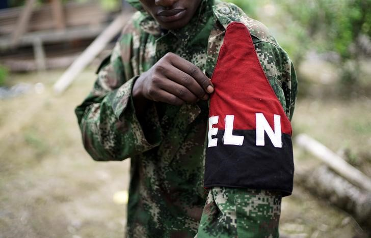 © Reuters. A rebel of Colombia's Marxist National Liberation Army shows his armband while posing for a photograph, in the northwestern jungles