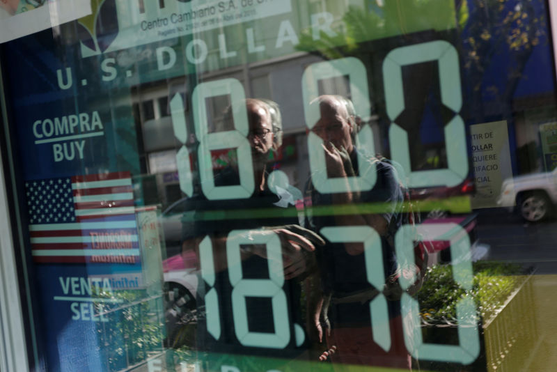 © Reuters. Tourists are reflected in a window as they look at a board displaying the exchange rate for Mexican peso and U.S. dollar at a foreign exchange bureau in Mexico City