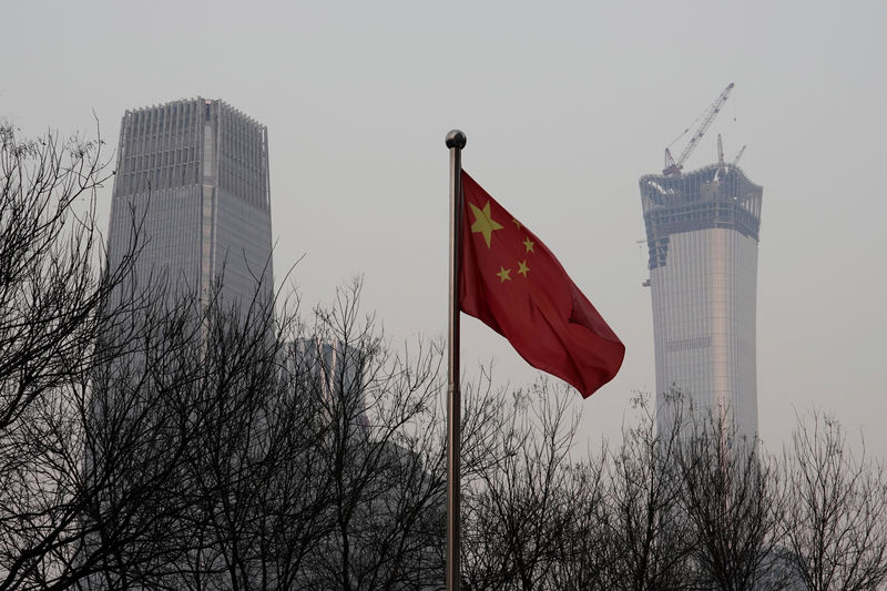 © Reuters. China World Trade Center Tower III and China Zun Tower under construction are pictured behind a Chinese flag in Beijing