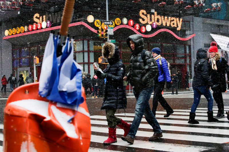 © Reuters. People walk around Times Square as a cold weather front hits the region, in Manhattan, New York
