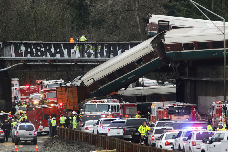 © Reuters. First responders are at the scene of an Amtrak passenger train which derailed and is hanging from a bridge over the I-5 in DuPont