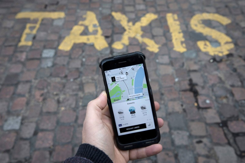 © Reuters. FILE PHOTO: A photo illustration shows the Uber app on a mobile telephone, as it is held up for a posed photograph, in London
