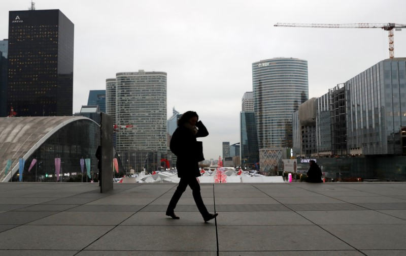© Reuters. A woman walks on the esplanade of La Defense, in the financial and business district of La Defense, west of Paris