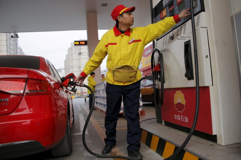 © Reuters. A gas station attendant pumps fuel into a customer's car at PetroChina's petrol station in Beijing