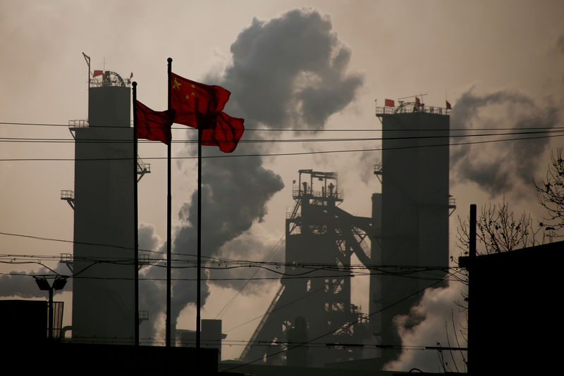 © Reuters. FILE PHOTO: Chinese national flags flutter near a steel factory in Wu'an