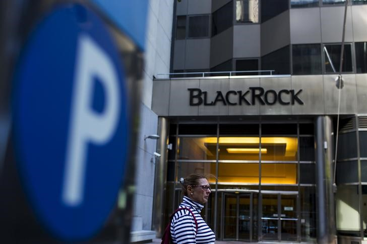 © Reuters. FILE PHOTO: A woman walks next to a BlackRock sign pictured in the Manhattan borough of New York