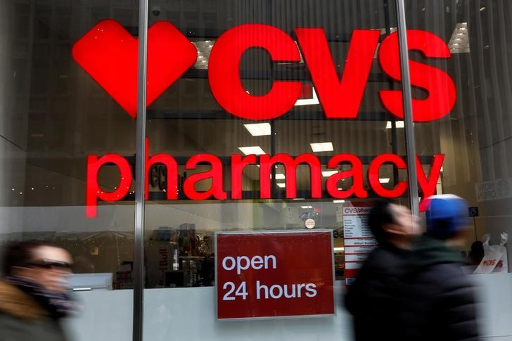 © Reuters. FILE PHOTO: People walk by a CVS Pharmacy store in the Manhattan borough of New York City