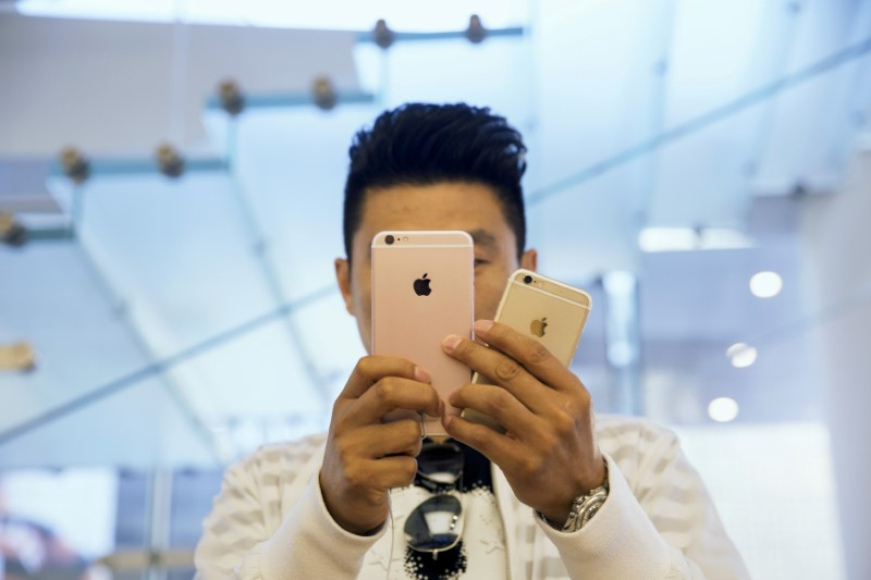 © Reuters. A man takes pictures as Apple iPhone 6s and 6s Plus go on sale at an Apple Store in Beijing