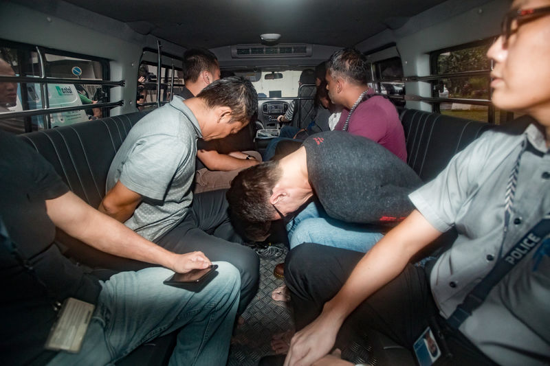 © Reuters. Suspects arrive in a van at the State Courts in Singapore