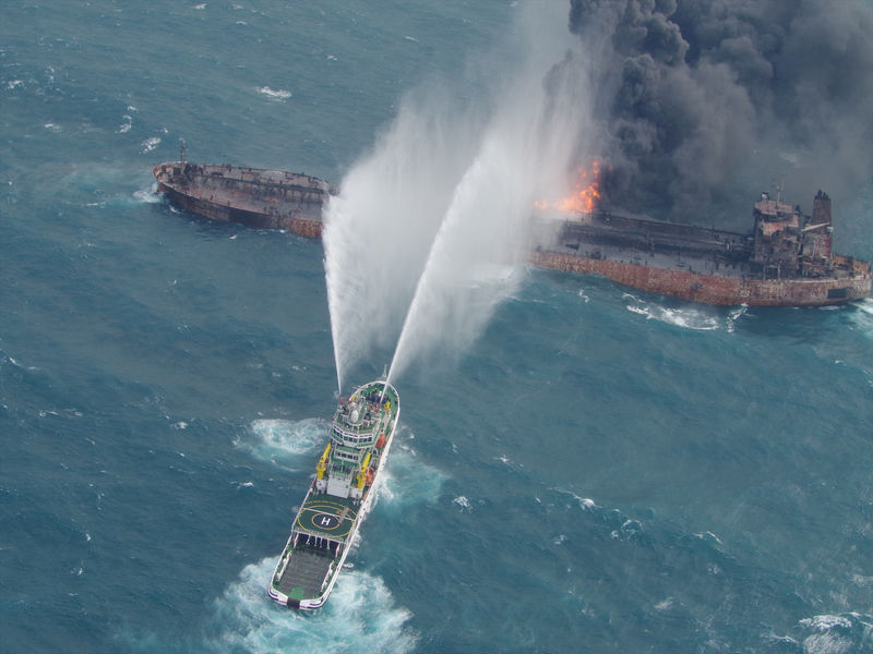© Reuters. A rescue ship works to extinguish the fire on the stricken Iranian oil tanker Sanchi in the East China Sea