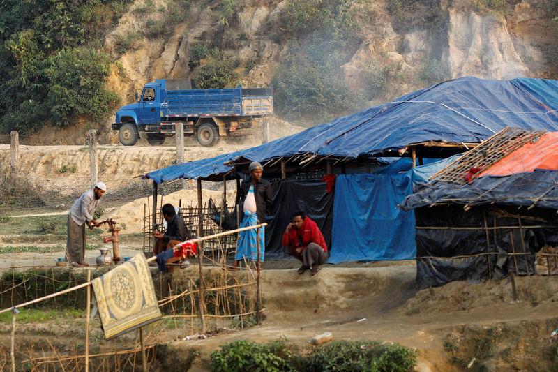 © Reuters. A Burmese vehicle drives behind Rohingya refugee camp at no man's land between Bangladesh-Myanmar border, in Cox's Bazar