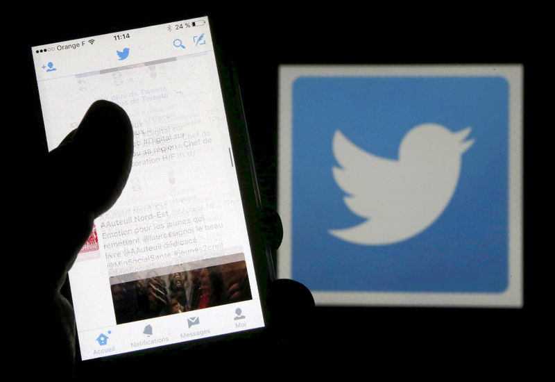© Reuters. FILE PHOTO: A man reads tweets on his phone in front of a displayed Twitter logo in Bordeaux, southwestern France