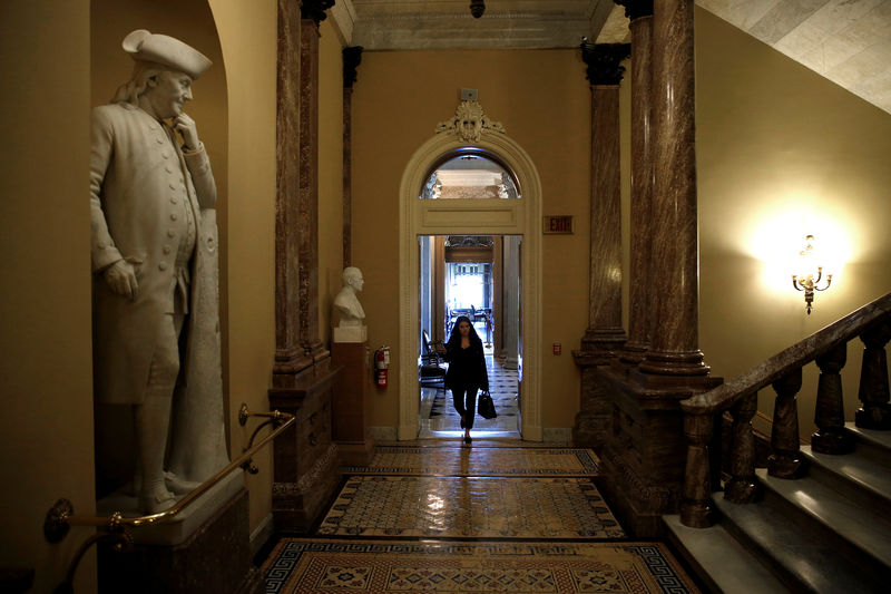 © Reuters. A woman walks past a statue of Benjamin Franklin after President Donald Trump and the U.S. Congress failed to reach a deal on funding for federal agencies on Capitol Hill in Washington