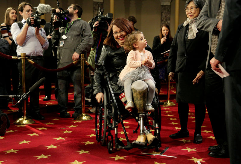 © Reuters. FILE PHOTO: Senator Duckworth (D-IL) carries her daughter Abigail during a mock swearing-in in Washington