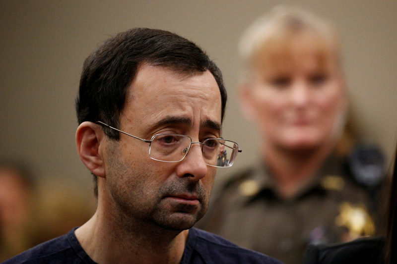 © Reuters. FILE PHOTO:    Larry Nassar, a former team USA Gymnastics doctor who pleaded guilty in November 2017 to sexual assault charges, stands with his legal team during his sentencing hearing in Lansing