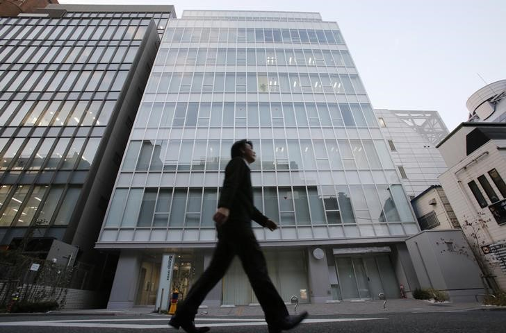 © Reuters. FILE PHOTO: A man walks past a building where Mt. Gox is housed in Tokyo