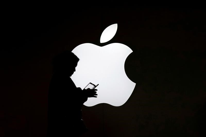 © Reuters. Женщина с мобильным телефоном на фоне логотипа Apple у магазина в Шанхае