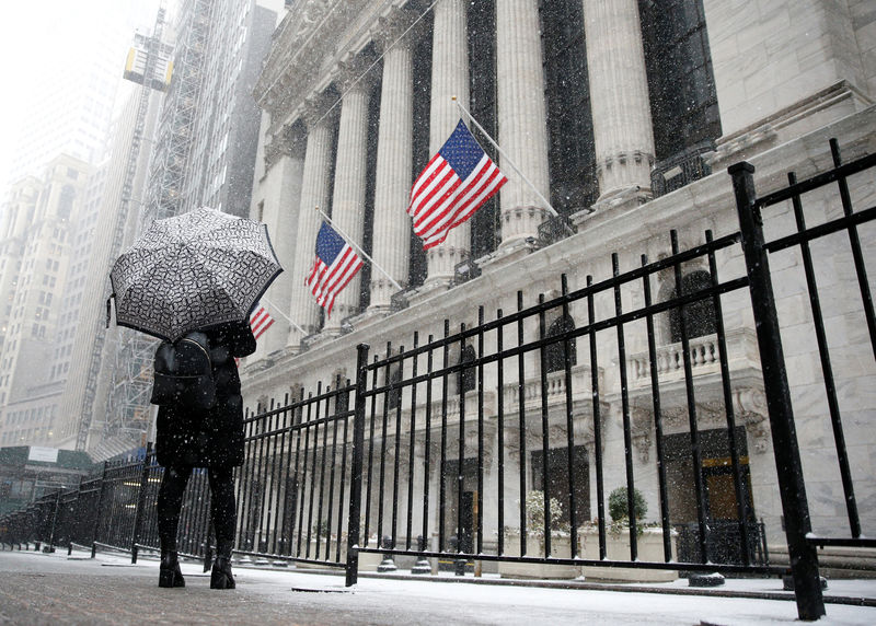 © Reuters. A woman looks up as snow begins to fall in front of the NYSE during the morning commute in New York