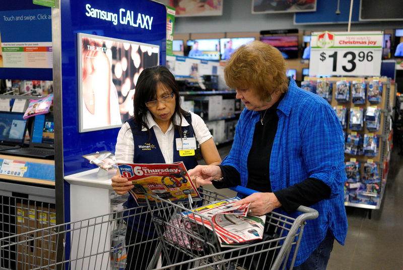 © Reuters. FILE PHOTO: A Walmart employee helps a customer navigate a sale flyer at the store in Broomfield