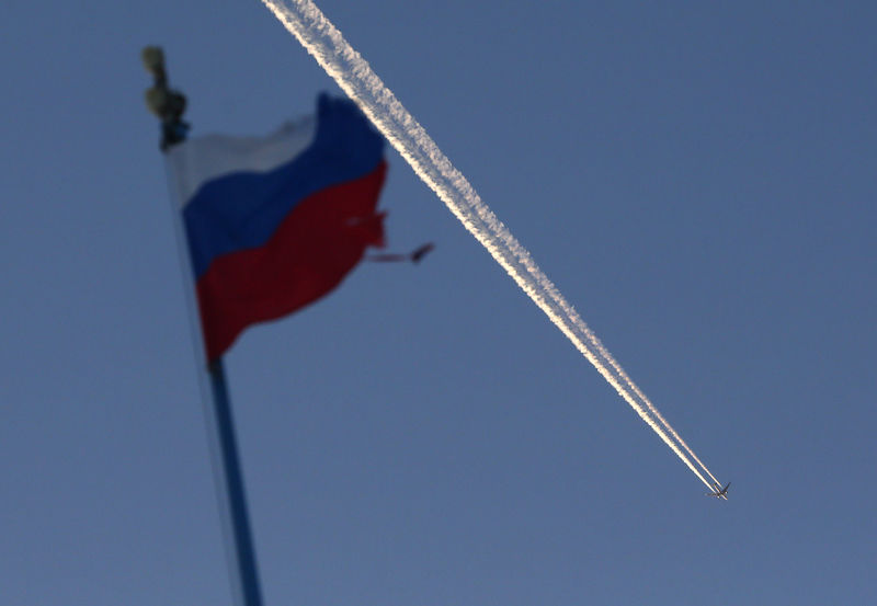 © Reuters. The Russian state flag flutters as a plane flies in the sky outside Krasnoyarsk